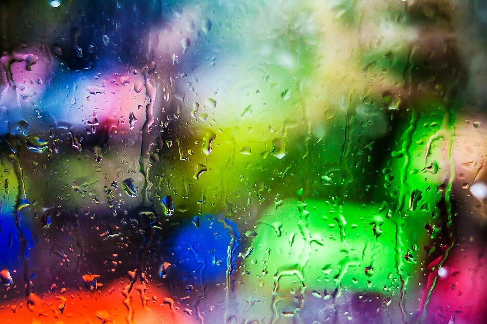 Raindrops covering the window, distorting the view to our colourful garden furniture.